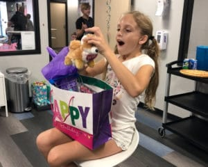 Girl opening presents at a birthday party.