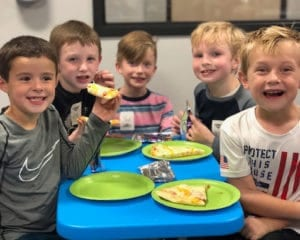 Kids eating pizza at a birthday party.